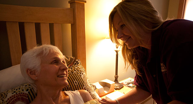 Elderly woman receiving at-home care by a Home Instead CAREgiver