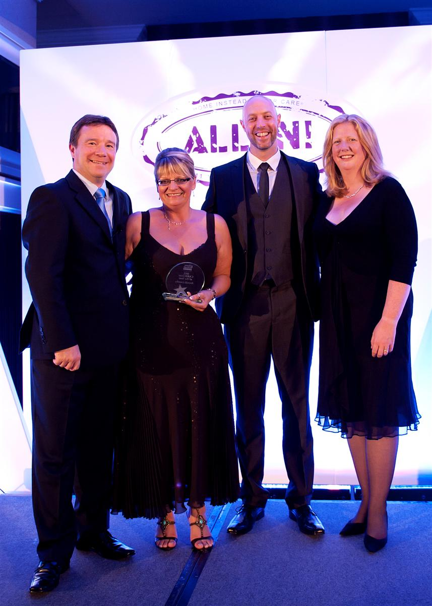 Amanda Loosely being congratulated by Home Instead UK managing directors and co-founders Trevor and Sam Brocklebank (far left and right) and Home Instead Oldham owner Mick Sheehan (second in from right) for her Caregiver of the Year award