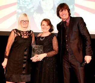 Home Instead East Nottingham & Melton Mowbray CAREgiver Ann Wiggett holding her 'Dementia Carer' award