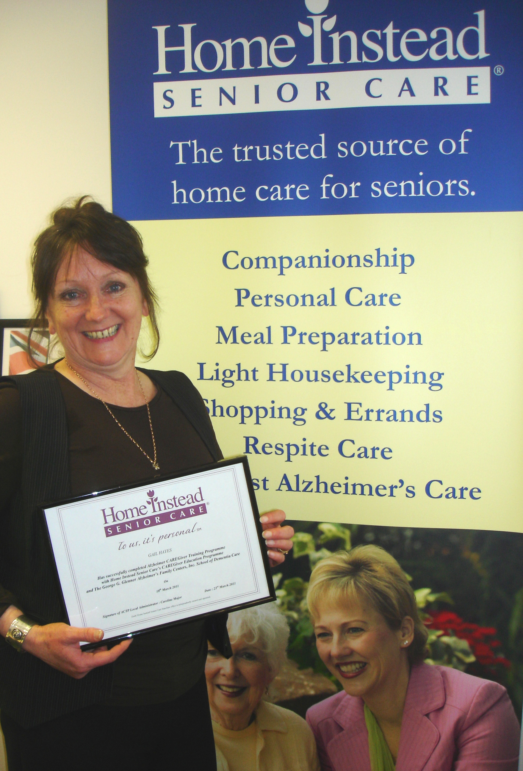 Home Instead High Wycombe CAREgiver Gail Haynes holding her Alzheimer's Advanced Training certificate