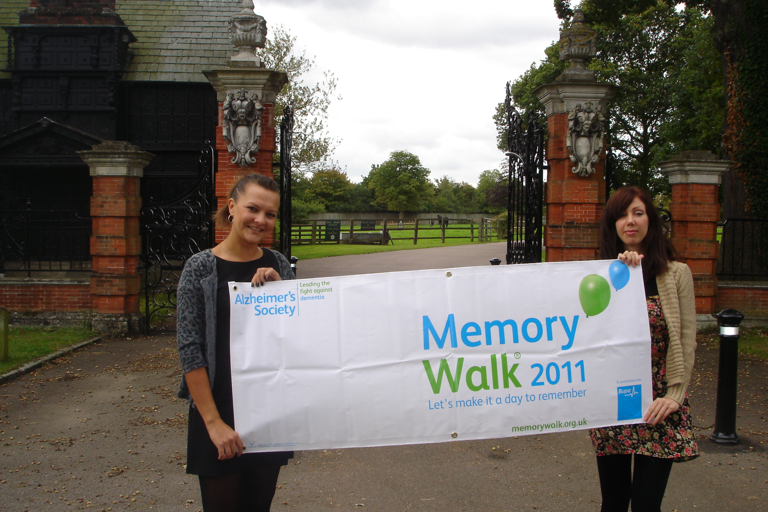 Home Instead South Buckinghamshire team members Zoe Smith and Vicky Swanwick holding the Memory Walk 2011 poster