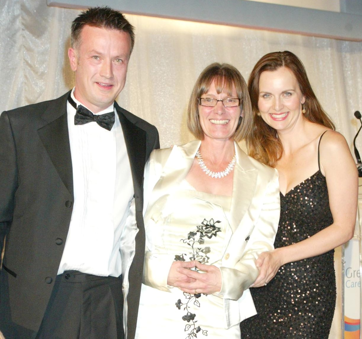 Home Instead Barnet CAREgiver Mary Hayes receiving her '2011 Home Care Worker' award from Jason Clayburn and TV presenter Debra Stephenson