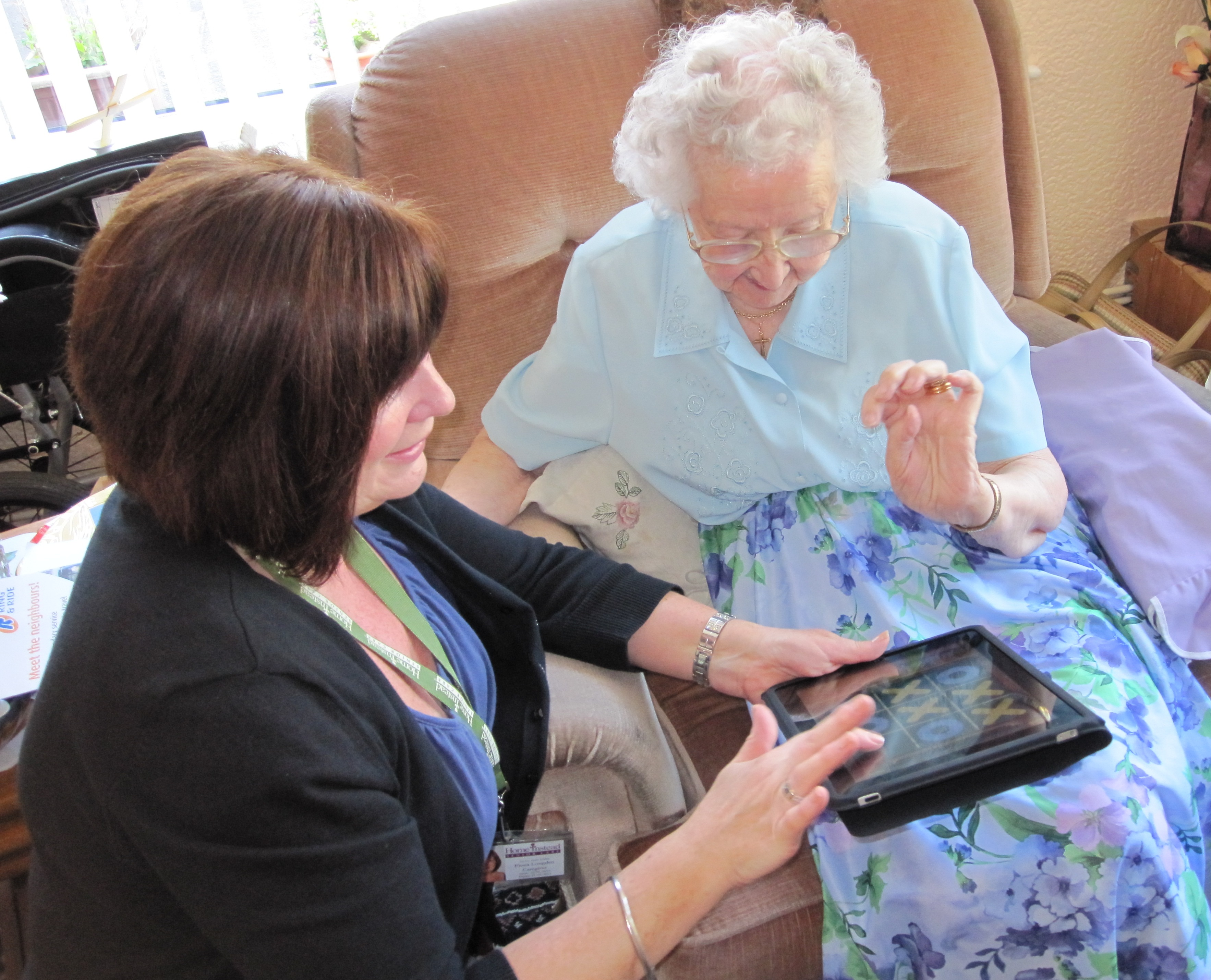 Home Instead Uppermill CAREgiver Fiona providing home care to her elderly client with the iPad