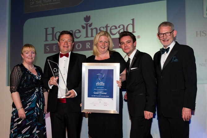 Home Instead Senior Care co-owners Sam and Trevor Brocklebank holding their trophy and certificate at the British Franchise Association HSBC Franchisor of the Year awards