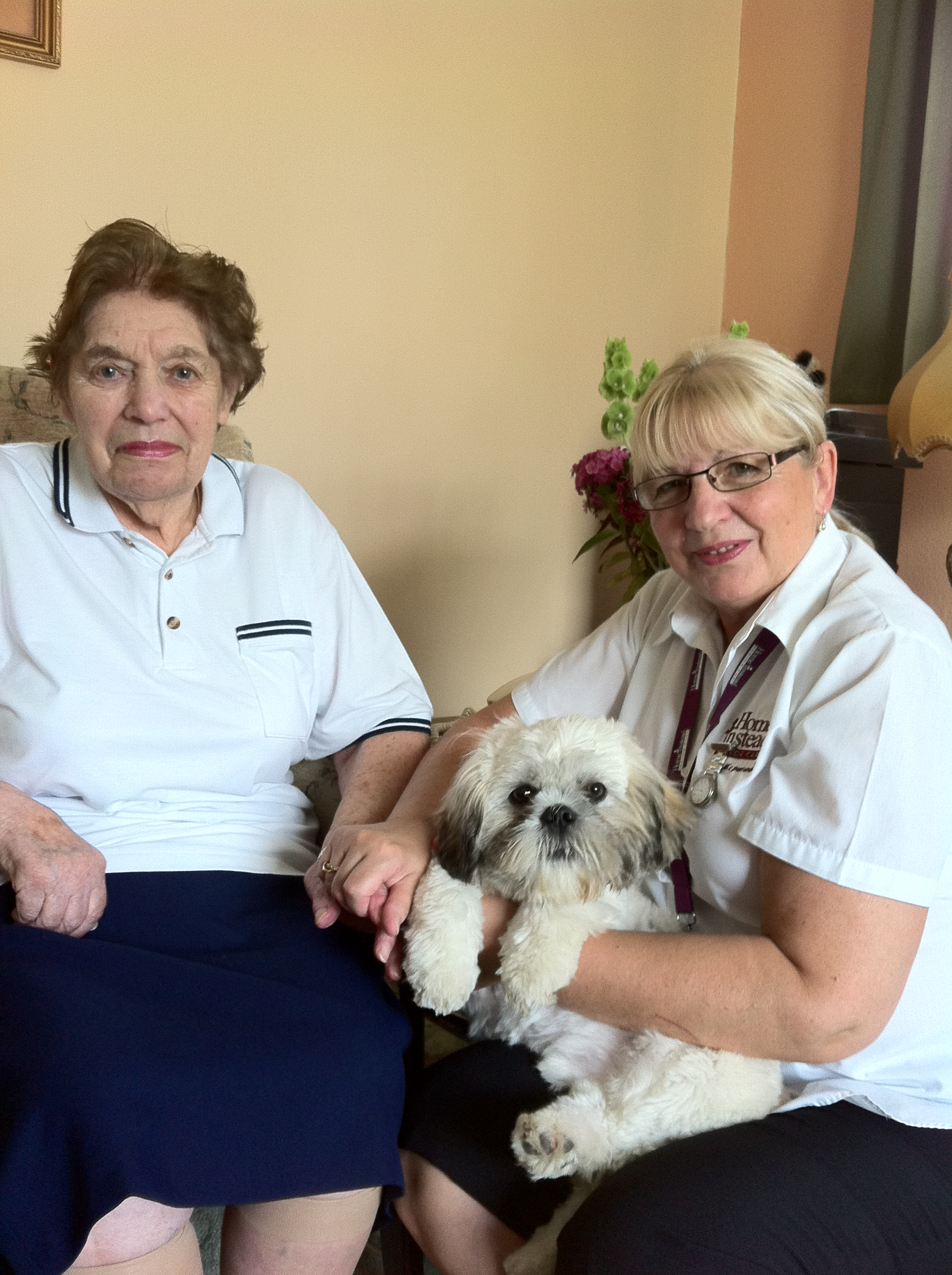 Home Instead South Lincolnshire CAREgiver Lynn Best presenting 6-month-old  Shih Tzu Archie to  85-year-old Home Instead client Betty Snell