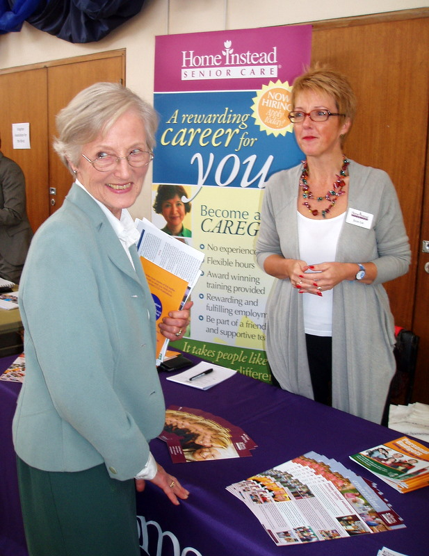 Reverend Helen Durrant-Stevensen next to the Home Instead stall at the Home Sweet Home information forum in Wimbledon and Kingston