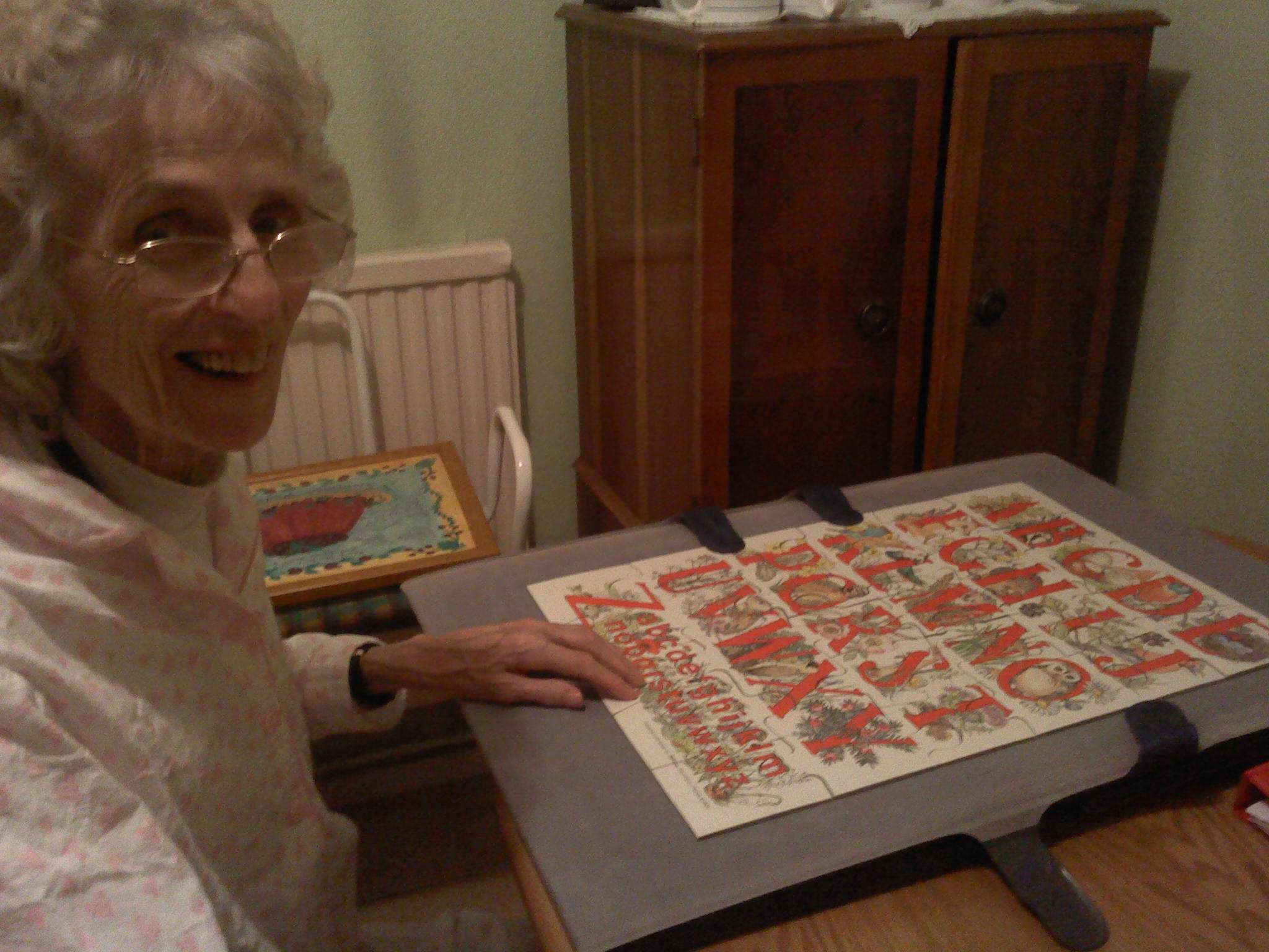 Home Instead St. Albans client Mrs Britton with the completed jigsaw her CAREgiver Althea Burrowes helped her organize