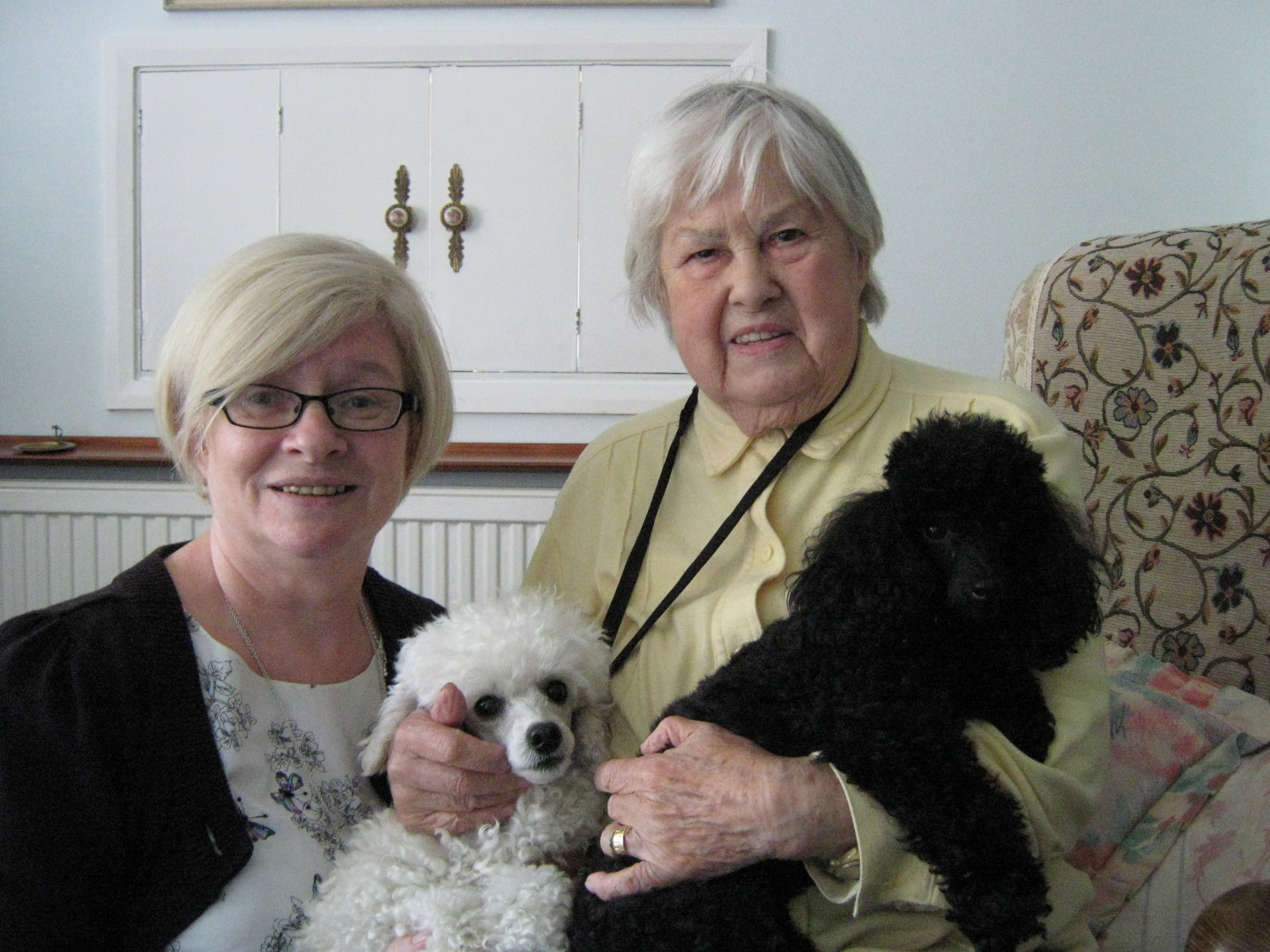 Home Instead Ruislip and Harrow Care Manager Marie Cavanagh with her black Poodle Annie and elderly client Mary Phillips next to her white Poodle Edna