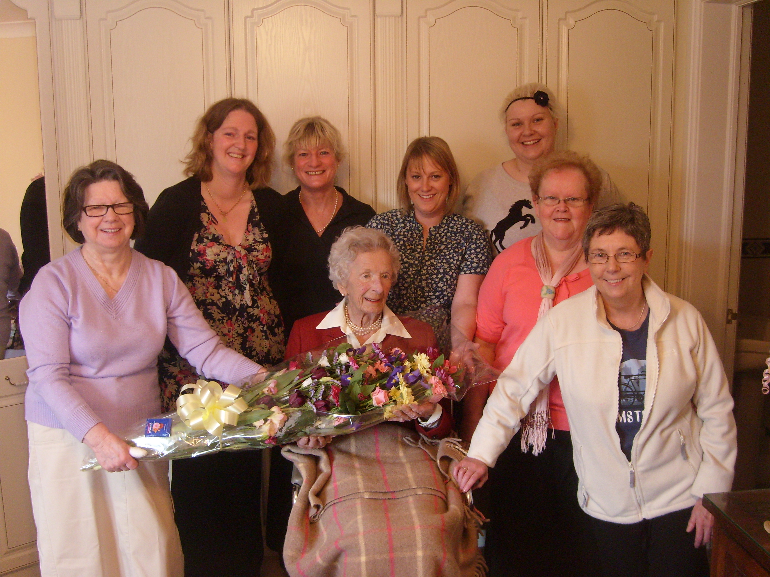 Home Instead Ripon crew members presenting a bouquet of flowers to client Mrs Leila Howell on her 102nd birthday