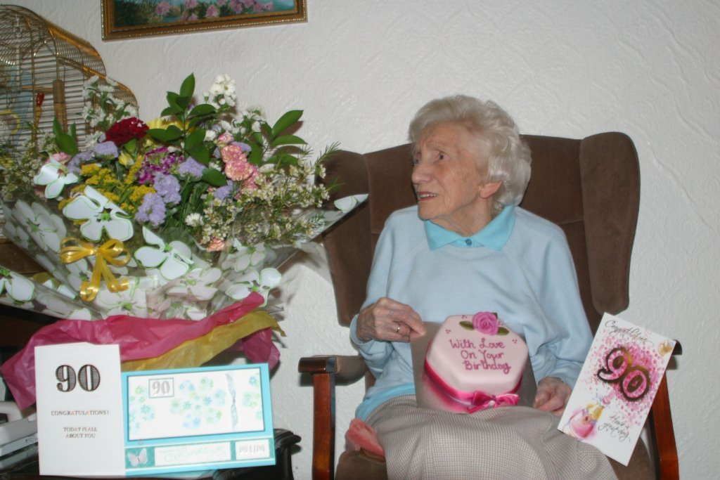 Home Instead Warrington client Mrs Muriel Jones next to her gifts on her 90th birthday greeted by her CAREgivers and family