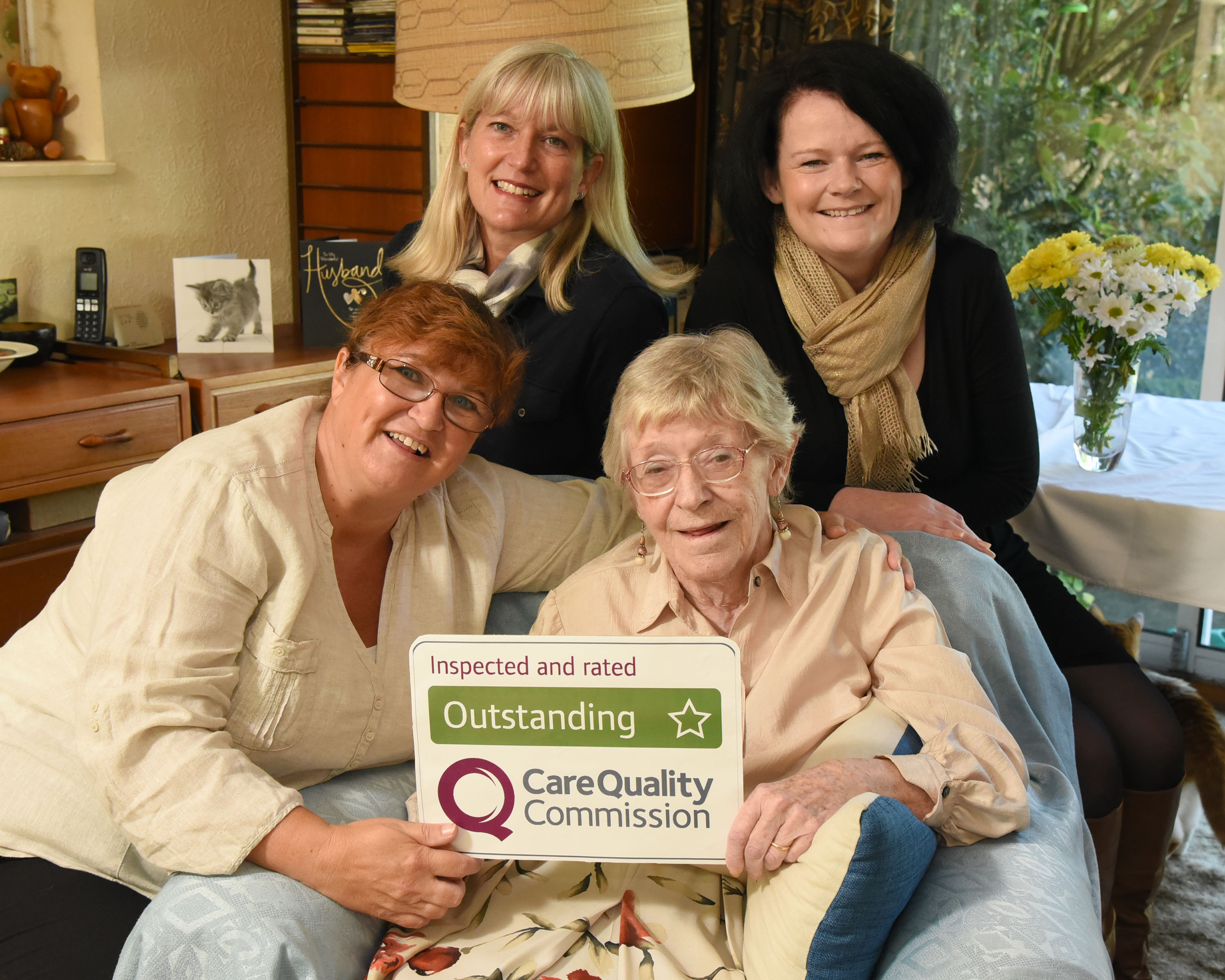 Home Instead Senior Care Cheltenham and Cotswolds team and elderly client holding their CQC Outstanding rating