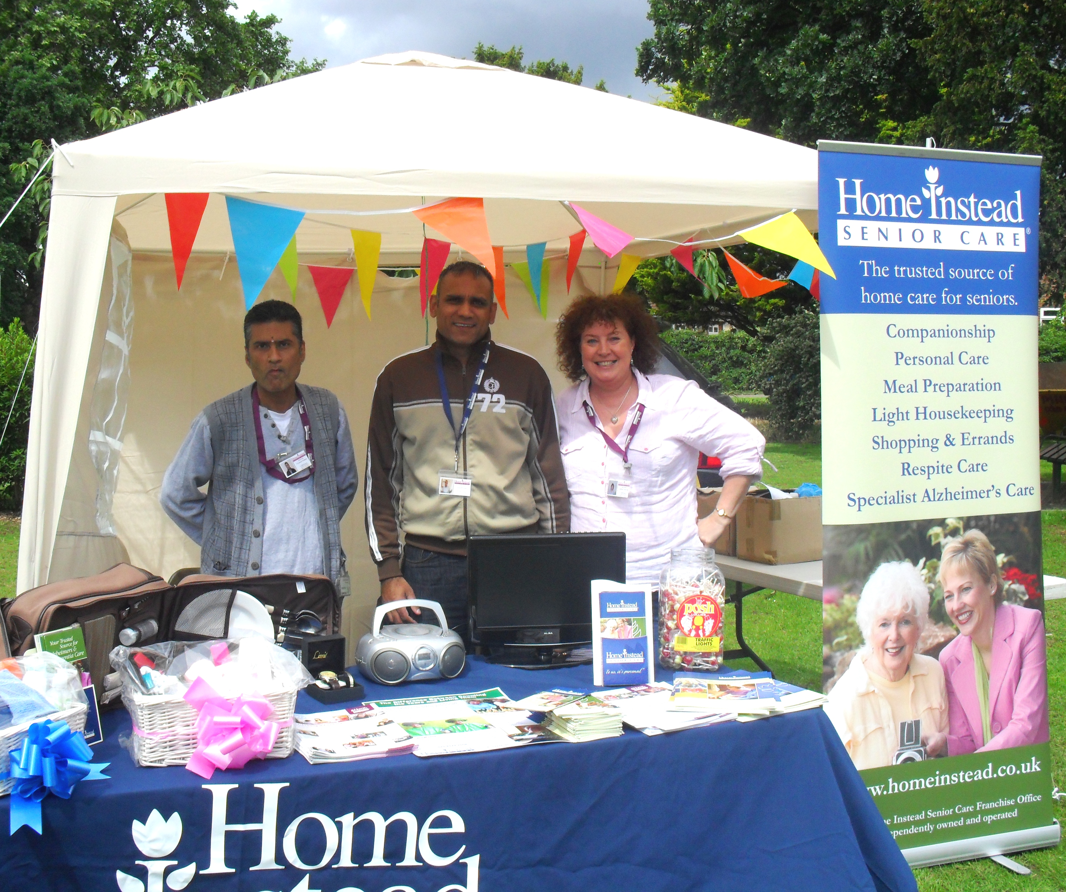 Home Instead Ealing owner Tony Hussein and team members in Home Instead's stall at the Hanwell Carnival