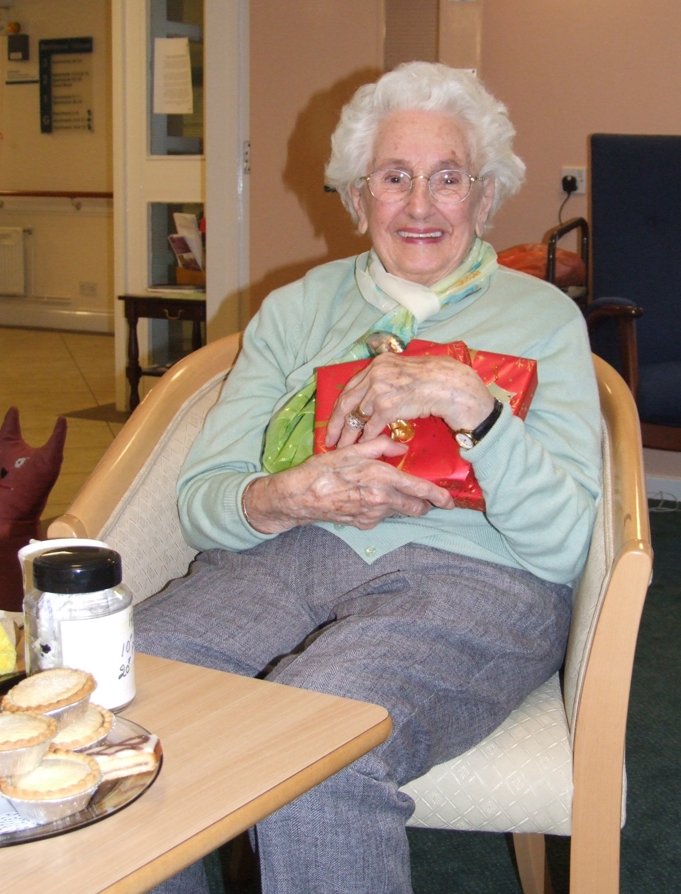 Home Instead Wimbledon & Kingston elderly client holding a wrapped Christmas gift