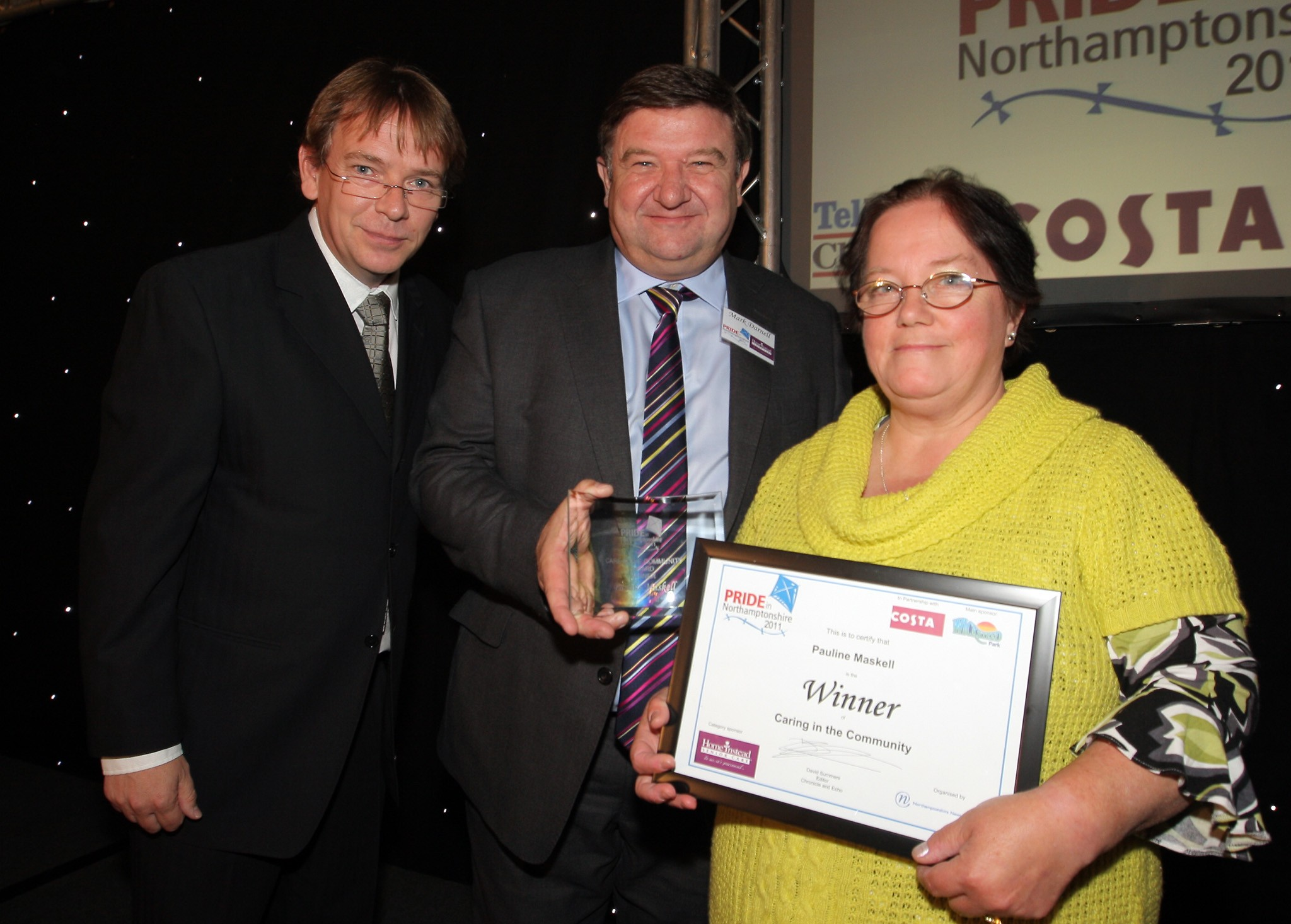 Home Instead East Northants owner Mark Darnell and celebrity guest Adam Woodyatt next to award winner Pauline Maskell