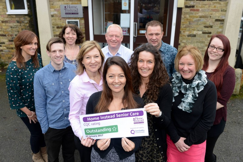 Home Instead Epsom and Mole Valley office team holding their CQC Outstanding rating
