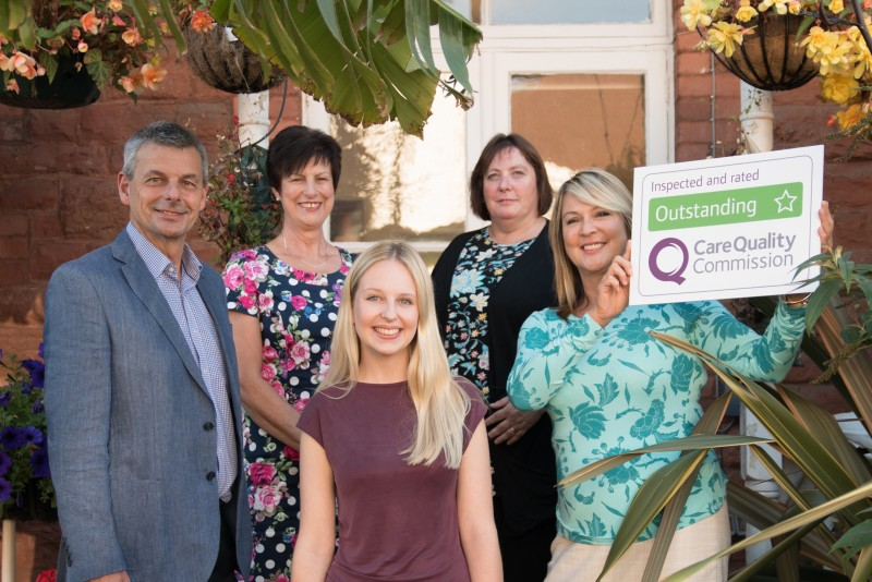 Home Instead Senior Care South Devon office team holding their CQC Outstanding rating