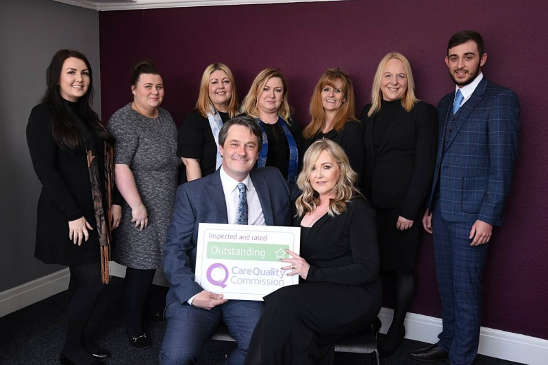 Home Instead Liverpool Central and North owners Kathryn and Andrew Erskine with team office holding their CQC Outstanding rating