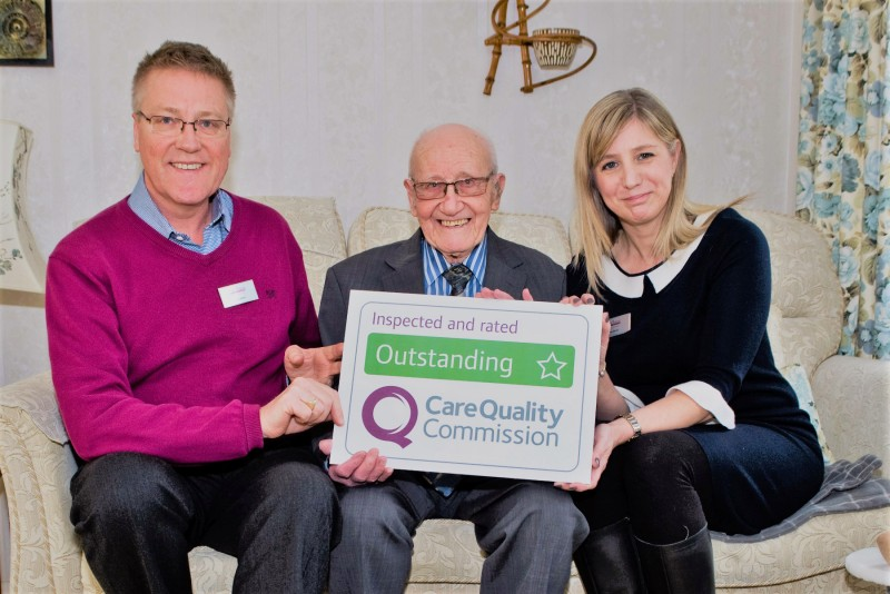 Home Instead Reigate & Tandridge owners Greg and Helen Brown and elderly client, holding their CQC Outstanding rating