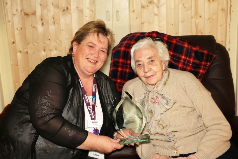 CAREgiver of the Year Lynne Higgins holding her award next to 84-year-old client Beryl