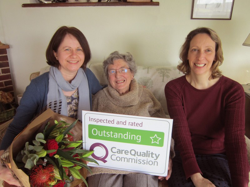 Home Instead Senior Care Farnborough, Farnham and Fleet team members and client holding their CQC Outstanding rating
