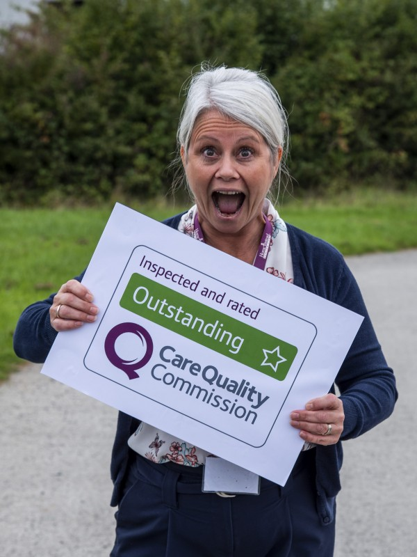 Home Instead North Devon office member holding their Outstanding CQC rating